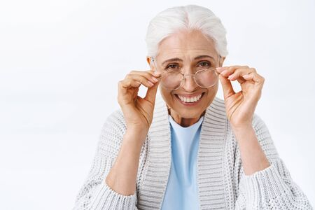 Cheerful old charming woman, happy grandmother, put on glasses to read book child, touching eyewear and smiling, laughing joyfully, pick prescription glasses at optician store for better vision