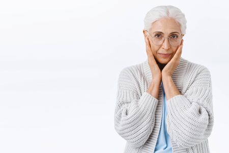 Aging, holidays and people concept. Charming senior lady with grey combed hair in glasses, touch cheeks as blushing or dreaming, smiling tenderly, taking care facial wrinkles, white background Foto de archivo - 138300142