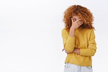 Embarrassed attractive modern redhead curly girlfriend in yellow sweater blushing as boyfriend behaving dumb in front of her friends, making facepalm and peek with one eye at awkward situation.