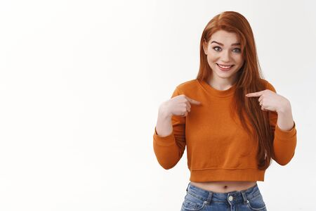 Are you kidding me, seriously. Surprised happy redhead cute girl pointing herself indicate chest questioned smiling pleased full disbelief unexpected picked chosen participate awesome event Foto de archivo - 138300513