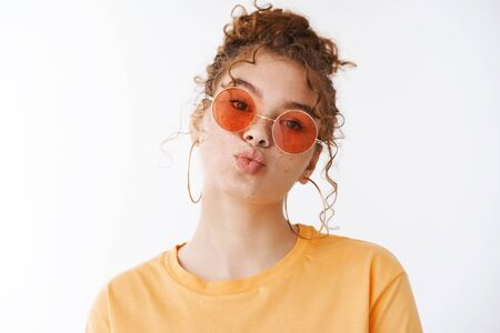 Silly cheeky stylish glamour redhead young 20s redhead girl freckles cheeks folding lips blow kiss mwah wearing sunglasses orange t-shirt look cute camera, standing white background fool around
