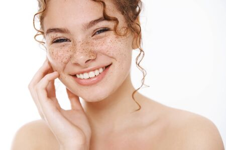 Headshot satisfied tender smiling redhead cute girl freckles curly-haired, standing naked white background laughing happily gently touch cheek look after skin like result apply cosmetology product 스톡 콘텐츠