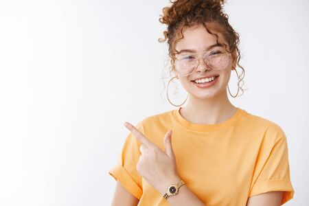 Stylish attractive carefree redhead teenage female college student having fun smiling broadly enjoying party show girls rule world rock-n-roll gesture grinning wearing trendy glasses orange t-shirt