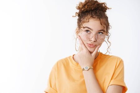 Thoughtful creative attractive redhead curly-haired female blogger thinking make-up new content ideas look focused take decision choice rubbing chin look hesitant upper left corner, white background