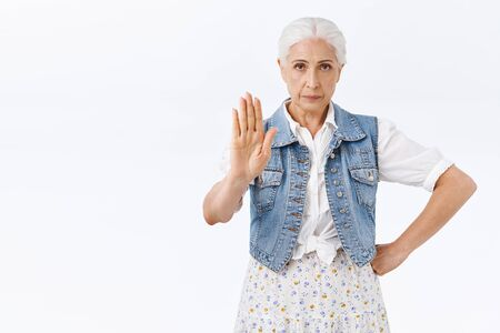 Stop right there young lady. Serious-looking pissed and displeased senior woman, old mother raise one hand in stop, prohibition or warn motion, smirk demand stay home, dont give permission Imagens