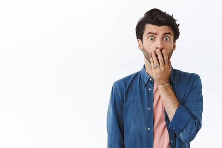 Troubled young bearded man, gasping cover opened mouth, stare worried and concerned, realise something terrible, standing anxious, express compassion as hear friend got in trouble, white background