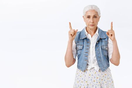 Pissed, irritated serious-looking old woman with grey hair combed, raising fingers pointing up, stare camera annoyed or displeased, standing bothered see strange promo, standing white background