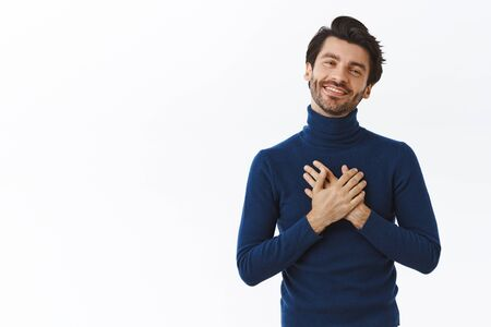 Handsome brunette man with beard in high neck sweater, press hands to heart and sighing as seeing heartwarming scene, look with admiration at something adorable, smiling happily, receive compliment Stock fotó