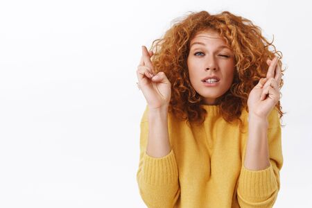 Close-up portrait hopeful, worried cute redhead curly woman in yellow sweater, stooping and grimacing with closed eyes and clenched teeth, cross fingers good luck, praying, waiting good results Archivio Fotografico