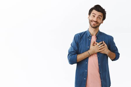 Charming, upbeat smiling man thanking from bottom of heart, press hands to chest and smiling cute as expressing gratitude for cool gift or appreciate help, standing white background flattered
