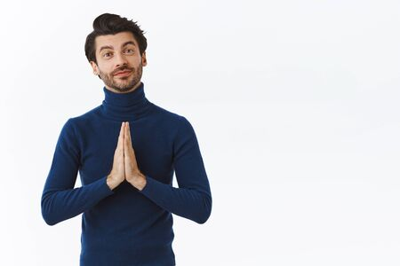 Handsome flirty bearded young man in blue high neck sweater, press palms together over chest in pray gesture, smiling as thanking someone, begging for advice or help, standing white background