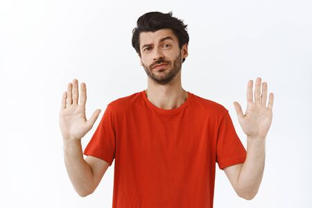 No thanks, I refuse. Arrogant good-looking bearded man in red t-shirt, raise arms in prohibition, forbid gesture, smirk and shake head displeased, rejecting bad offer, white background