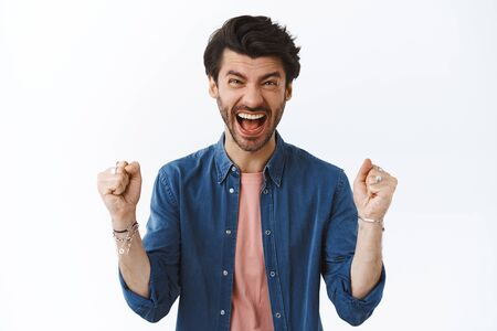 Excited, happy cheerful handsome man receive excellent news, clench fists, pump it and yelling yes, hooray as team won prize, achieve goal, celebrating success, triumphing over white background