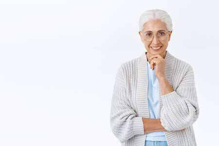 Waist-up studio shot happy smiling senior lady, grandmother considering buying flat riterement home or travel abroad for holidays, touch chin and grinning curious or satisfied, stand white background