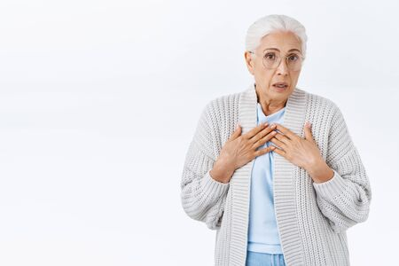 Oh dear. Concerned senior lady with grey hair in glasses and warm cardigan looking overwhelmed and shocked, press hands to chest, exhale nervously and stare camera shocked, heard troublesome news 版權商用圖片