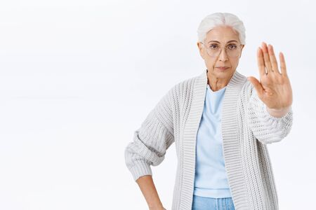 Serious and strict old woman, grandmother forbid, stretch arm forward in stop, rejection or prohibition gesture, look camera determined and confident, dont allow son smoke, standing white background