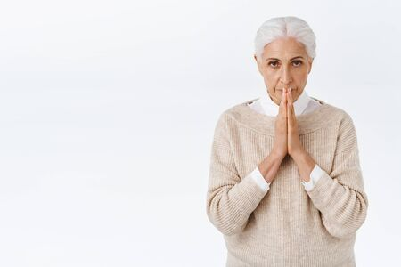 Stressed, worried elegant senior woman, old lady with grey combed hair, touch lips to hands in pray, searching answers god, supplicating, making wish or awaiting important thing happen