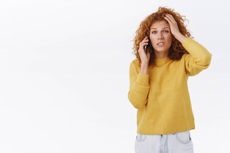 Girl have complicated, troublesome conversation via smartphone. Perplexed, indecisive redhead curly woman in yellow sweater, touch head, frowning, grimacing puzzled, talking on mobile phone