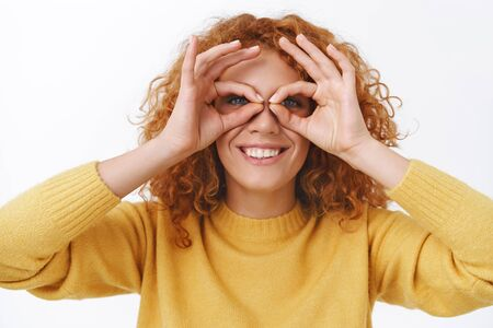Staying kid no matter what age you are. Cheerful, playful cute redhead silly woman with curly hair, making glasses with fingers and looking through, having fun, smiling joyfully, white background