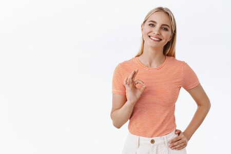 Girl says you doing great. Satisfied attractive blond feminine woman in striped t-shirt, show okay, approval sign and smiling, nod in agreement as giving permission, think choice is excellent