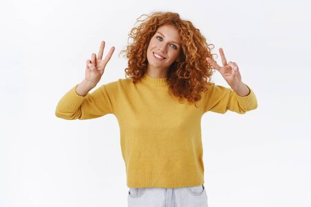 Tender, lovely and feminine redhead curly woman, smiling happy and showing peace signs, tilt head joyfully, making quotation marks as talking sarcastically, standing white background