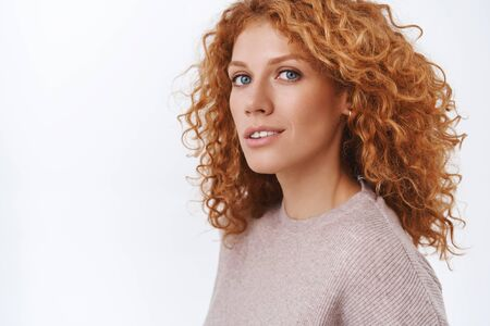 Close-up feminine gorgeous redhead curly woman in beige blouse standing half-turned over white background, turn head to camera with sensual, happy and coquettish expression, flirting Reklamní fotografie