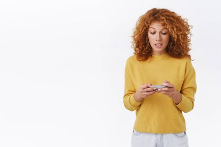 Girl trying carefully pass level, standing determined and focused, make intense look on mobile display, holding smartphone horizontally, playing phone game, want beat friends score, white background