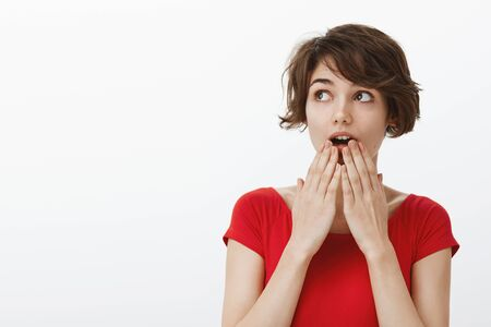 Surprised timid tender cute millennial woman short haircut open mouth wondered gasping impressed shocked look upper left corner ambushed hold palms lips intrigued white background Zdjęcie Seryjne