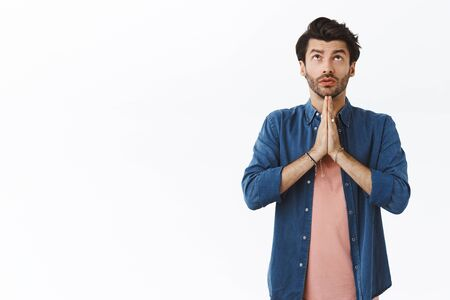 Handsome young caucasian bearded guy praying god, look up in sky and making wish, clasp hands together over chest, supplicating, beggingr Lord for good new year, standing white background