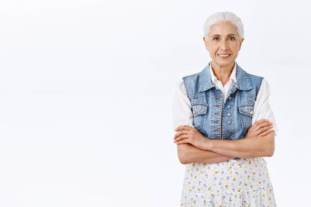 Happy smiling old woman with white hair combed, wearing stylish modern outfit, cross hands over chest, grinning joyfully, express positivity and enthusiasm, healthy and carefree lifestyle Reklamní fotografie