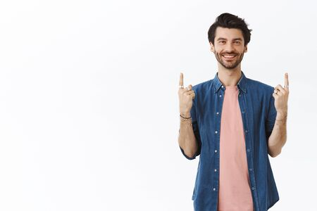 Handsome, outgoing smiling man with beard, wearing pink t-shirt, shirt, pointing up and looking camera, showing gifts he bought, invite people visit link, recommend cool party, hang-out spot