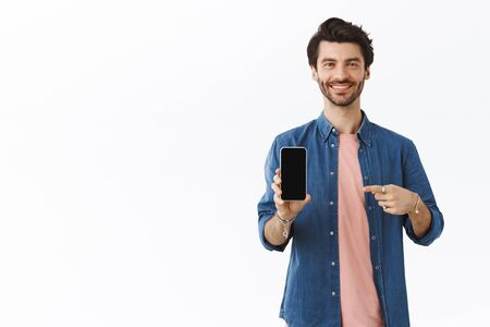 Pleased, confident cheeky bearded man bragging, showing photos on smartphone, holding phone, pointing mobile display and grin satisfied, recommend good online store, white background