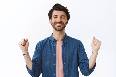 Relieved, happy successful young bearded man, close eyes smiling satisfied, clench arms as fist pump, say yes or celebrating achievement, feeling confident, triumphing over white background