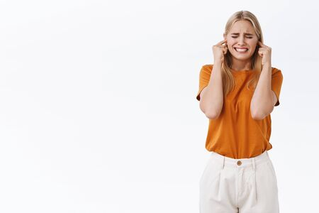 Stressed and uneasy miserable good-looking blond girl in orange t-shirt with tattoos, close eyes and clench fists distressed, shut ears from hearing loud annoying noise, stand white background Stock Photo