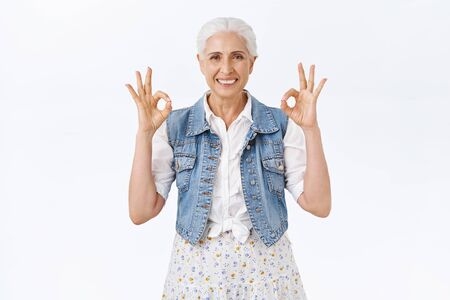 Chill, unbothered happy old woman with grey haircut, wear denim vest, dress, showing everything okay, ok gesture, smiling have things under control, assure all fine, white background