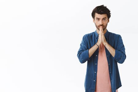 Handsome young bearded guy begging for permission or favor, asking help as clasp hands together near lips and look sincere camera, making promise or want something, stand white background