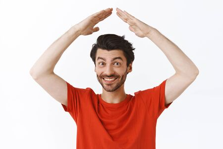 Waist-up portrait handsome young man with bristle, wear red t-shirt raising hands above head as making house roof, smiling joyfully, cant wait celebrate holidays in family circle, white background