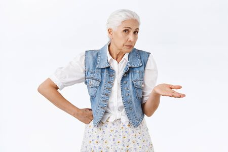 Questioned, annoyed and irritated senior woman look pissed and disappointed with dismay or scorn, shrugging raise one hand and looking with disapproval at camera, smirk judgemental Stock Photo