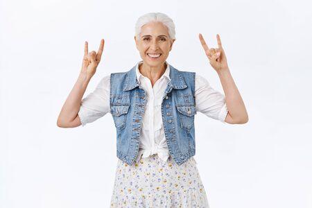 快乐的现代,时髦的酷奶奶,与孙子的乐趣听摇滚n-loll音乐告诉美好的老天在重金属音乐会,显示岩石标志和微笑的无忧无虑,白色背景