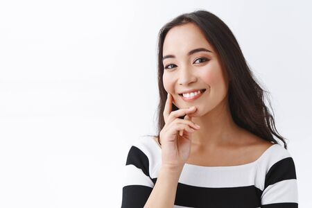 Close-up tender and feminine pretty woman with clean skin no clogged pores, without blemishes, touching cheek and smiling joyfully, gazing camera, tilt head gently, stand white background