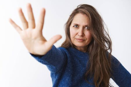 Stop right there young lady. Displeased strict and bossy female parent in 50s pulling palm towards camera in forbid gesture looking displeased and dissatisifed, restricting and forbidding something