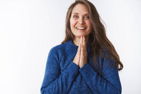Namaste, middle-aged woman feeling relaxed and happy holding palms pressed together near chin in pray, smiling friendly, thanking for help being grateful, posing in blue sweater over white background