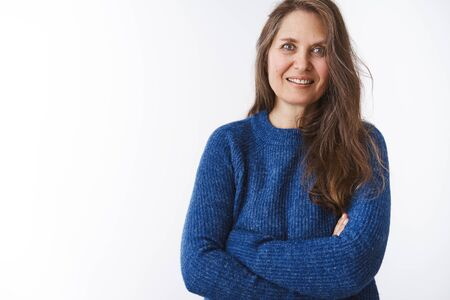 Confident charming middle-aged lady in warm sweater cross hands against chest and smiling at camera having faithful and hopeful attitude things be better posing over white background