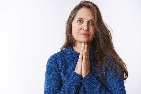 Serious-looking desperate middle-aged woman in need begging for help looking with supplication camera holding hands in pray, asking show mercy, apologizing hopefully against white background