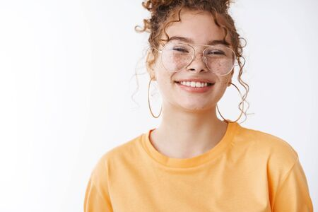 Satisfied good-looking grinning friendly young redhead curly-haired teen girl smiling broadly eating favorite meal standing pleased joyfully looking camera wearing glasses orange t-shirt