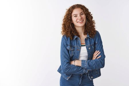 Charming carefree queer girl redhead freckles acne prone skin having fun smiling roadly accepting flaws standing carefree unbothered white background laughing friendly looking camera cross arms chest