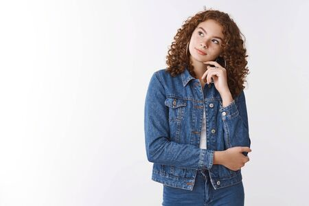 Dreamy thoughtful cute ginger girl curly-haired wearing denim lean head look upper left corner thinking making choice mind decide what food order, standing white background relaxed chill
