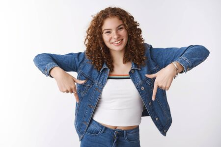 Attractive carefree young girl curly-haired redhead freckles pimples, smiling friendly raise index fingers pointing down suggesting look downwards check out awesome promo, white background Stock Photo