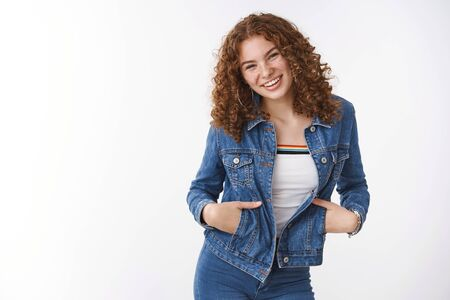 Easy-going charming friendly young teenage girl redhead with freckles pimples wear denim jacket hold hands pockets laughing broadly having fun positive mood standing white background