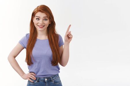 Cute outgoing caucasian redhead woman with long ginger hair, wear purple t-shirt, pointing upper right corner, invite visit corporate page, online store, shopping place, offer check-out event